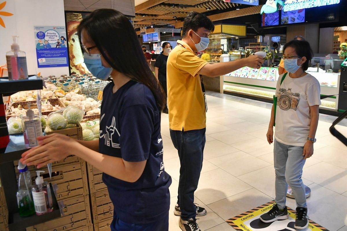 Shoppers undertake temperature screening and sanitise their hands before entering FairPrice Finest at Clementi Mall on April 22, 2020.