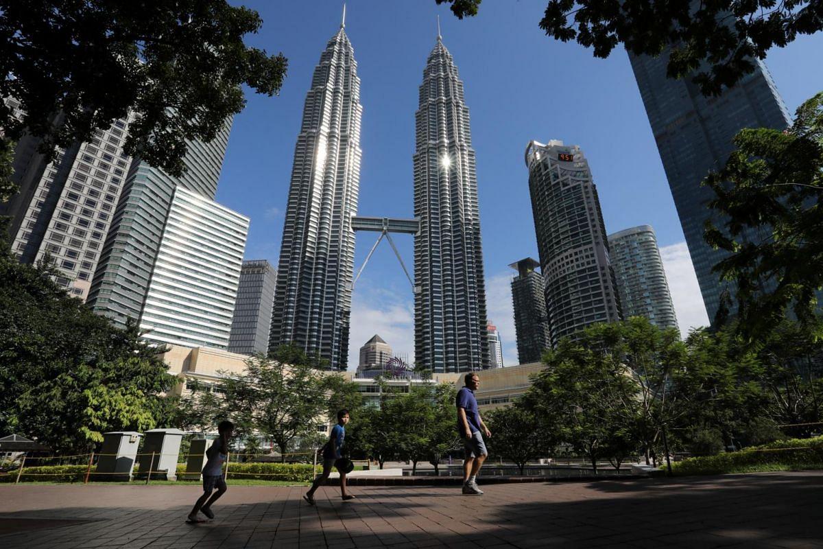 A family jog at a park near Petronas Twin Towers in Kuala Lumpur on May 4, 2020.