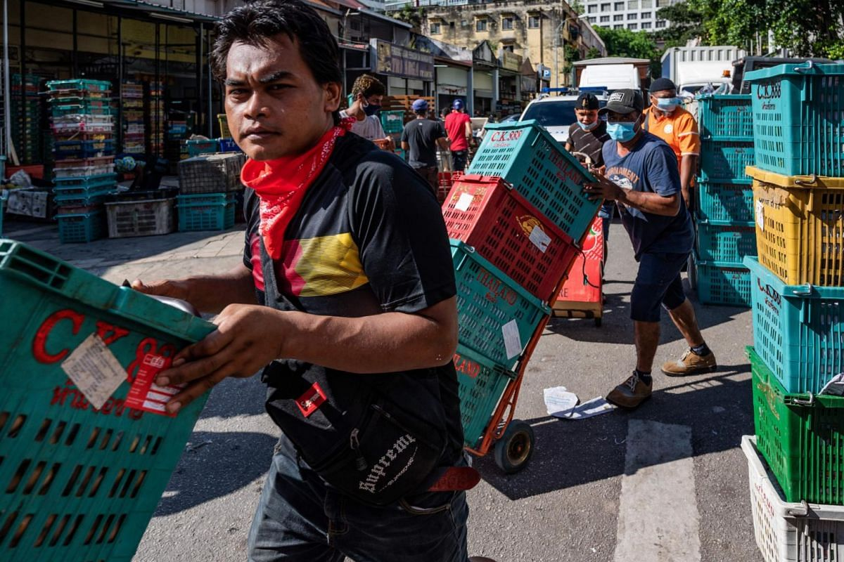 Workers wearing face masks push empty crates at a fruit market in Kuala Lumpur on May 4, 2020.