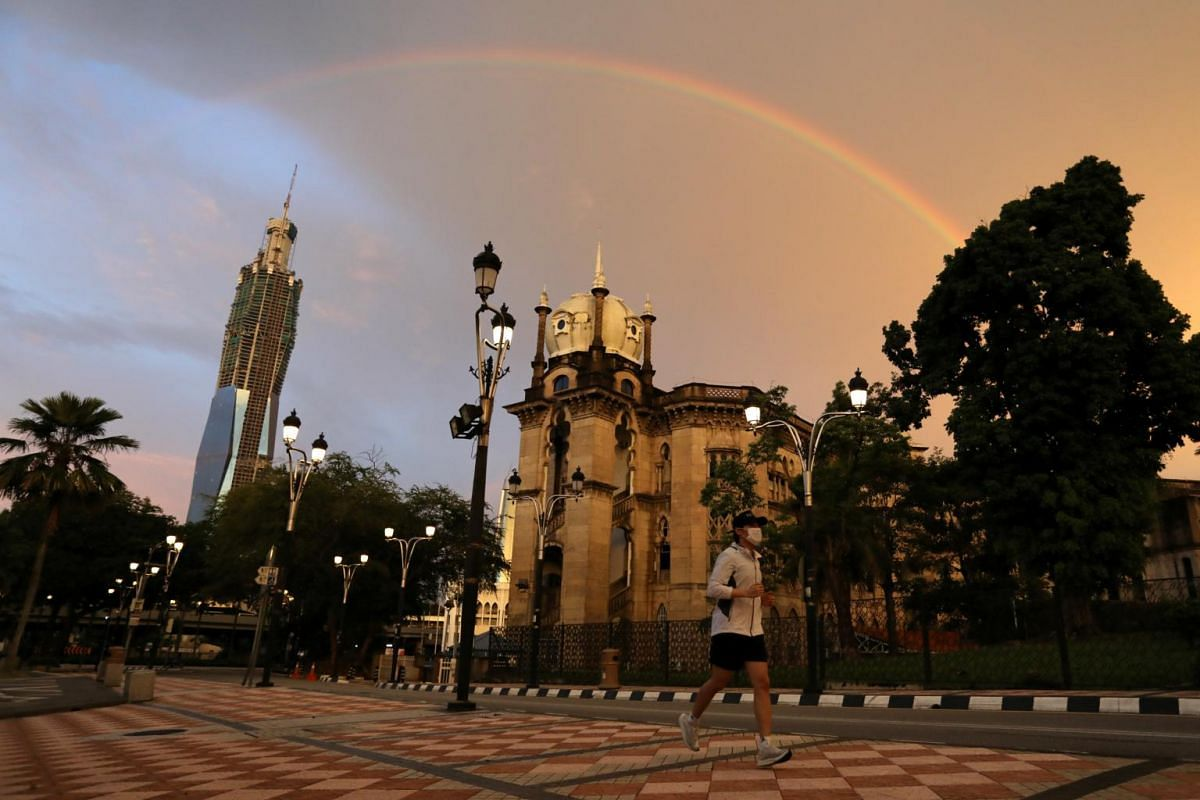 A man wearing protective face mask jogs under a rainbow in Kuala Lumpur on May 4, 2020.