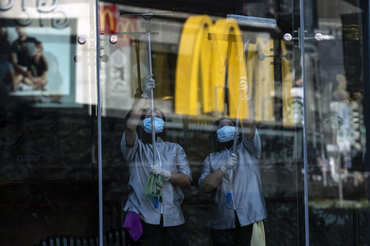 Workers clean a glass panel at a shop in Kuala Lumpur on May 4, 2020.