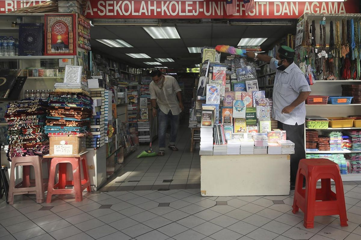 Workers prepare their shop for business after Malaysia eased coronavirus restrictions in Kuala Lumpur on May 4, 2020.