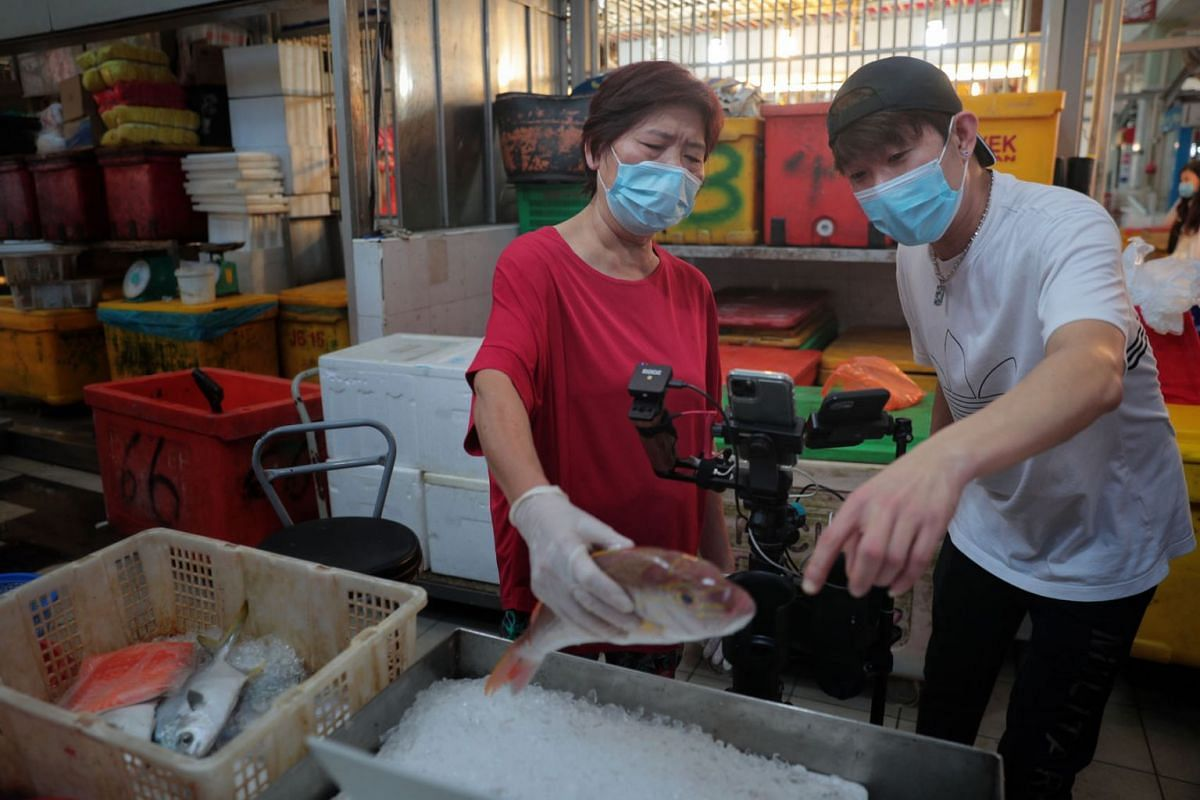 Ms Janet Tiou, 68, of 81 Sheng Yu stall at Tekka Market received some tips on selling her seafood via livestream on May 5, 2020, from Mr Max Kee, 37, of Lian Huat Seafood. PHOTO: THE STRAITS TIMES/JASON QUAH