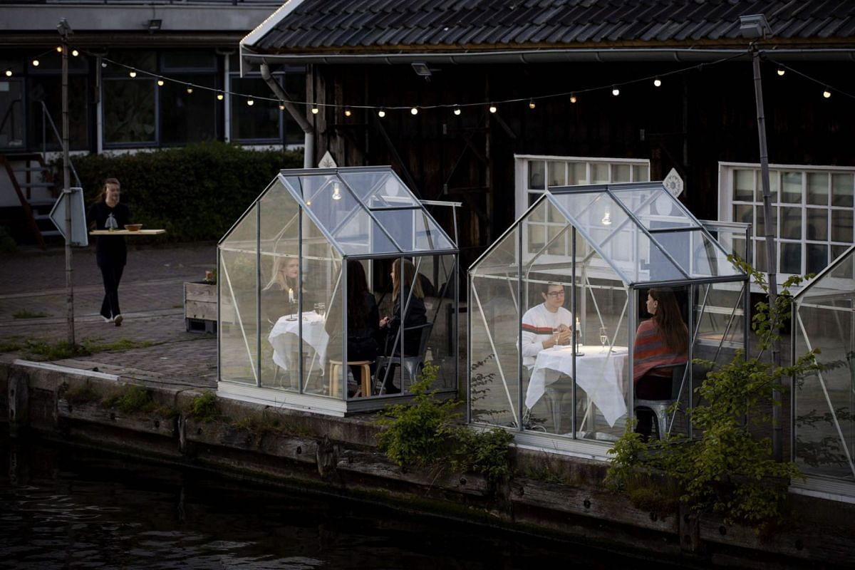 People have dinner in a so-called quarantine greenhouses in Amsterdam, on May 5, 2020 as the country fights against the spread of the COVID-19, the novel coronavirus. PHOTO: ANP VIA AFP