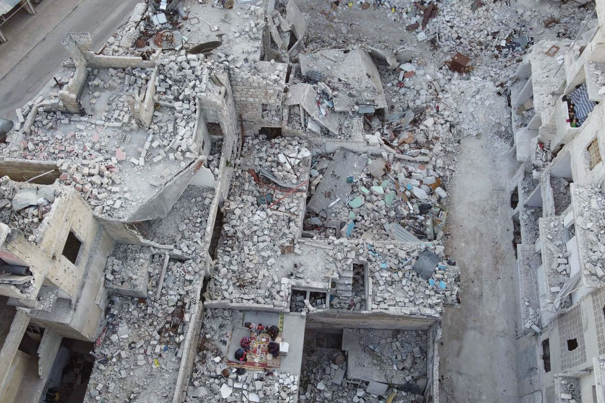 """This picture taken on May 4, 2020 during the Muslim holy fasting month of Ramadan shows an aerial view of members of the displaced Syrian family of Tareq Abu Ziad breaking their fast together for the sunset """"iftar"""" meal, in the midst of the rubble of"""