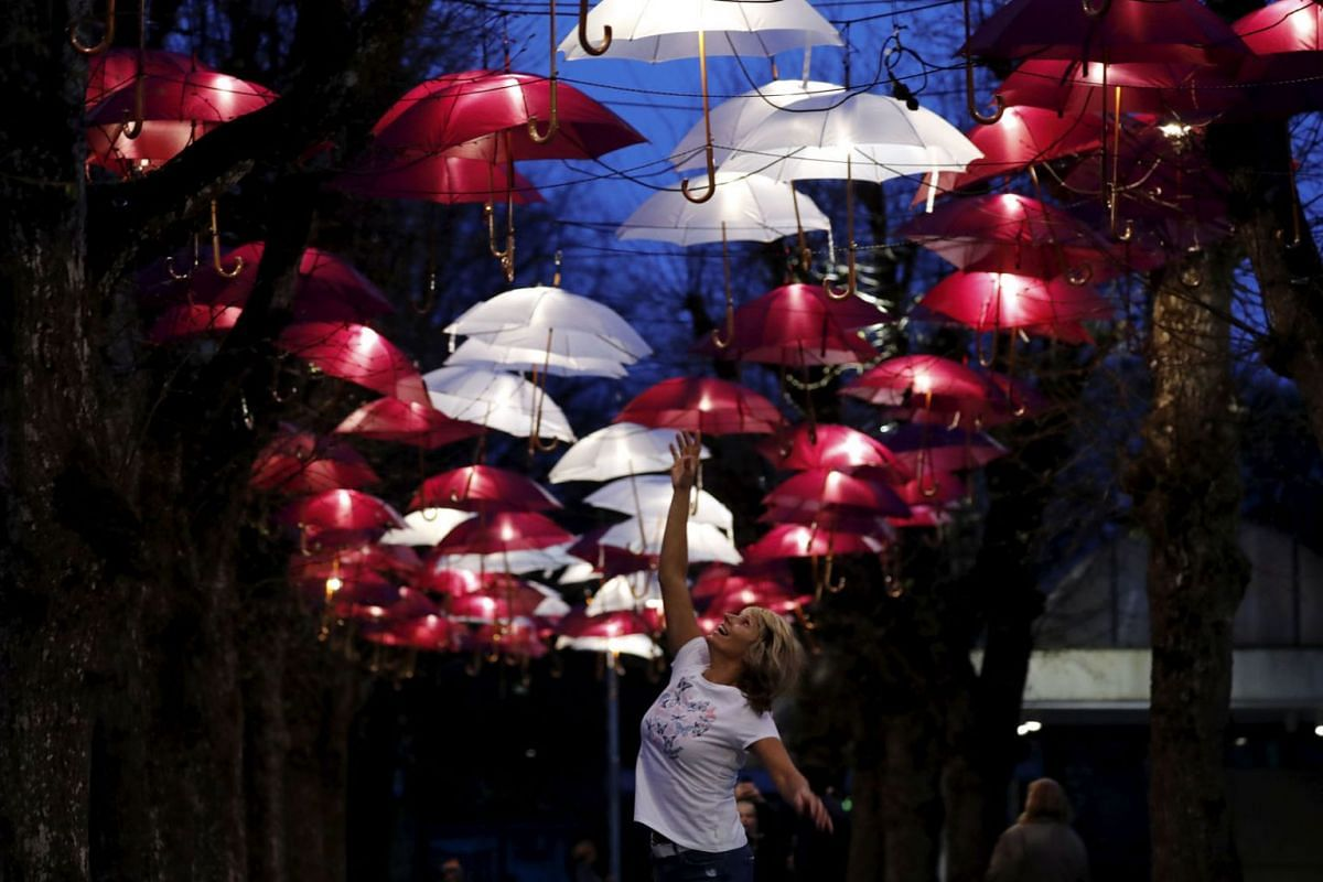 A woman jumps under an umbrellas installation in the colors of the national flag, in Ogre, Latvia, May 5, 2020, during the coronavirus pandemic. PHOTO: EPA-EFE