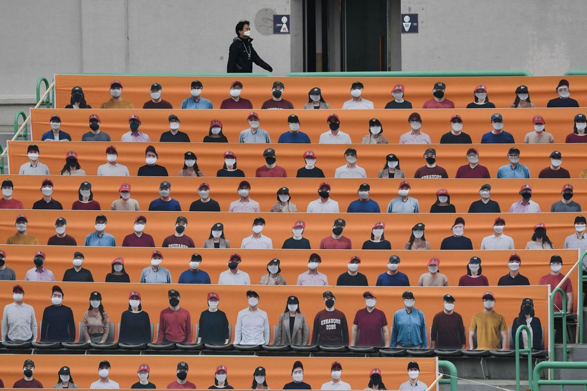 A man walks past banners depicting spectators in the stands prior to South Korea's new baseball season opening game between SK Wyverns and Hanwha Eagles in Incheon on May 5, 2020. PHOTO:  AFP