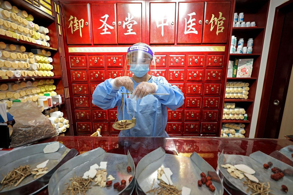 Physician Li Huarong preparing Chinese herbs for her patients on May 5, 2020. She received advance bookings for acupuncture treatments after Saturday's announcement that they could resume. PHOTO: THE STRAITS TIMES/WANG HUI FEN