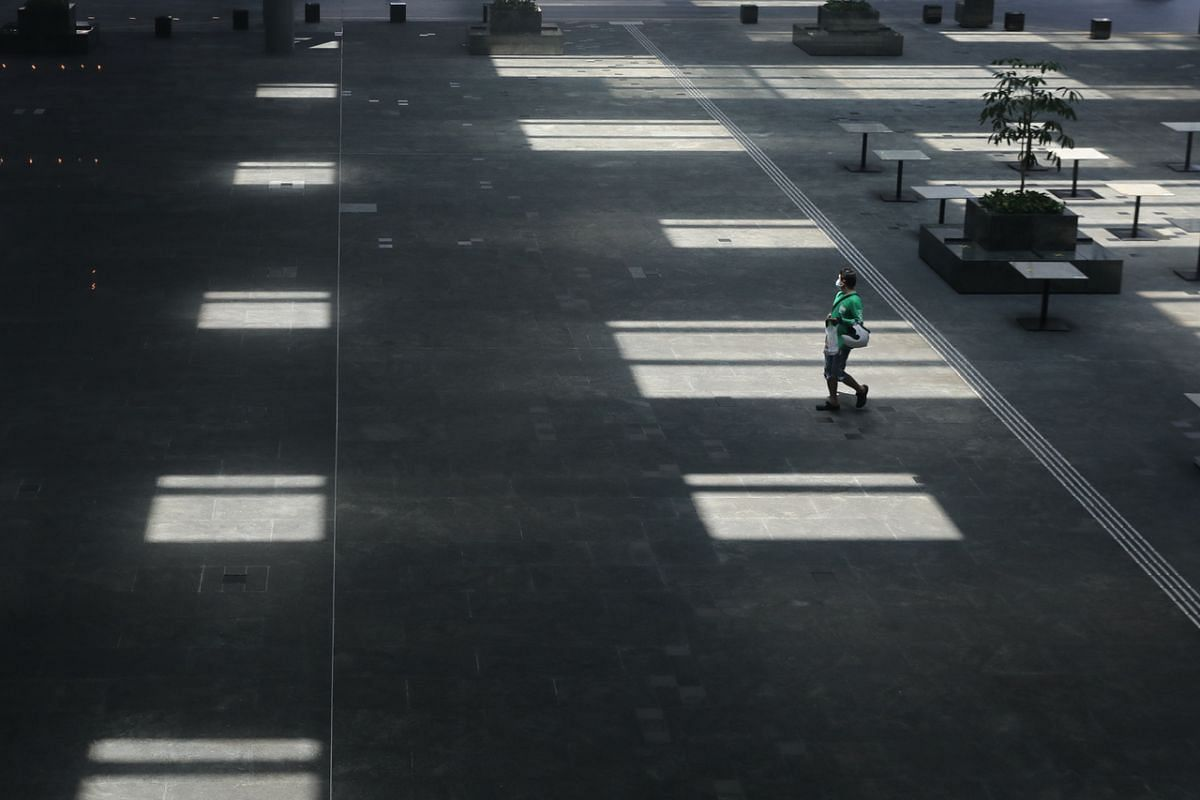 A GrabFood delivery person walks through an empty Asia Square on May 5, 2020.
