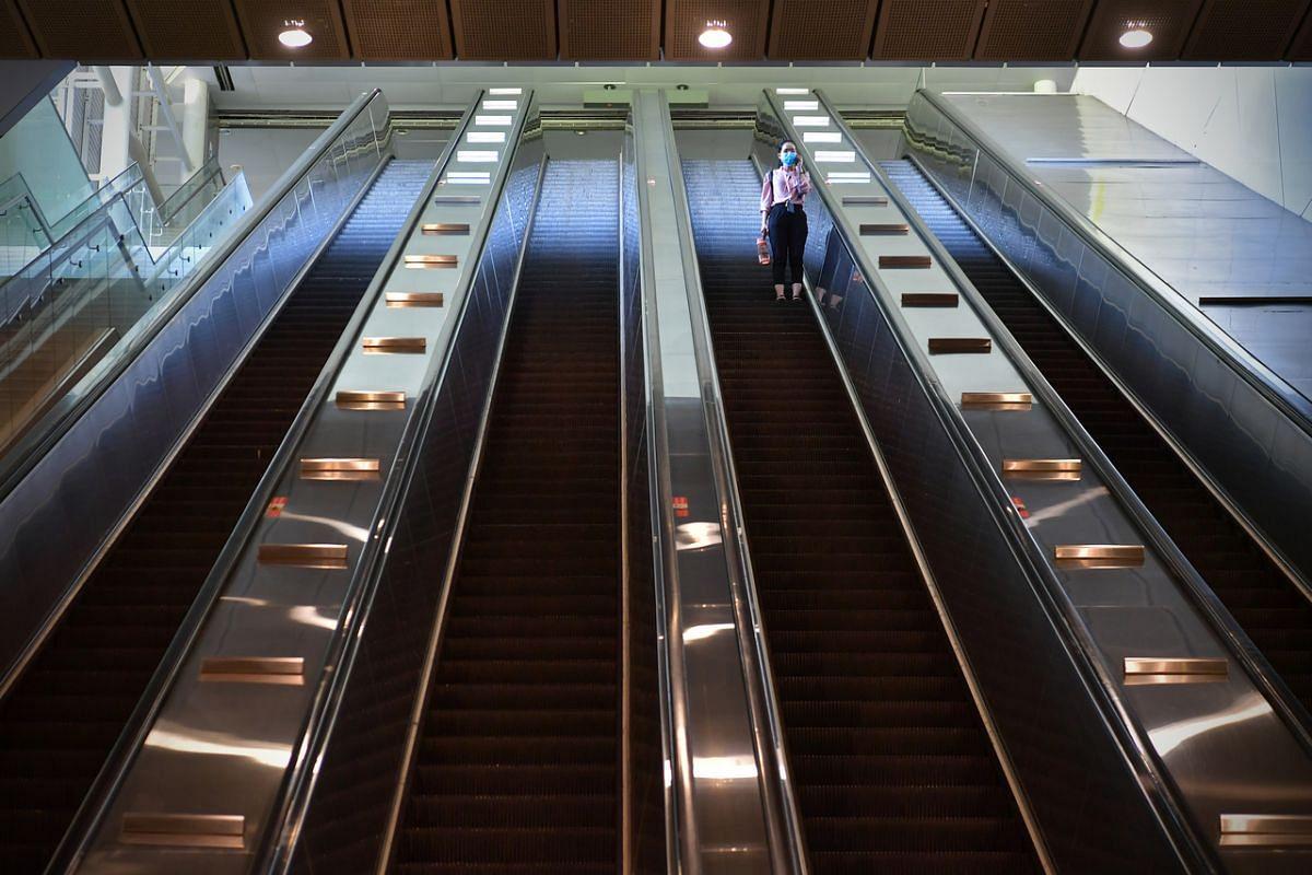 A lone commuter takes the escalator at Buona Vista MRT on April 18, 2020.