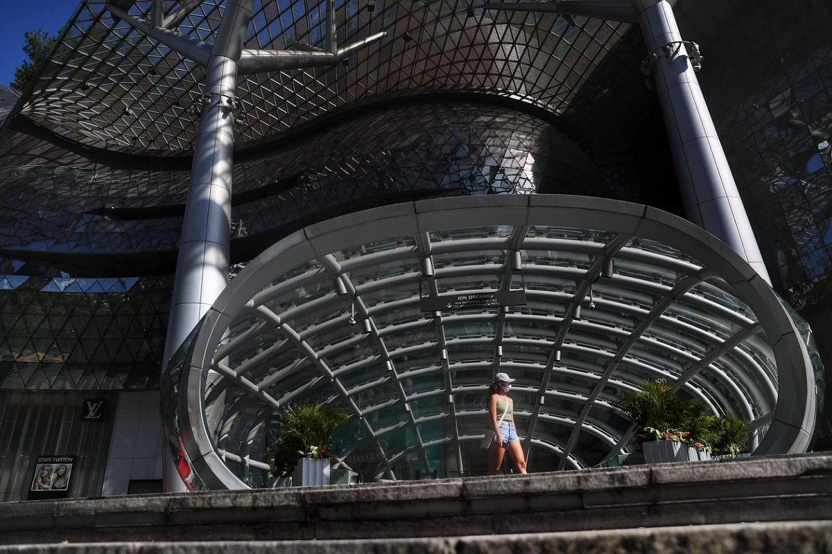 A woman walks outside ION Orchard Mall on May 9, 2020.