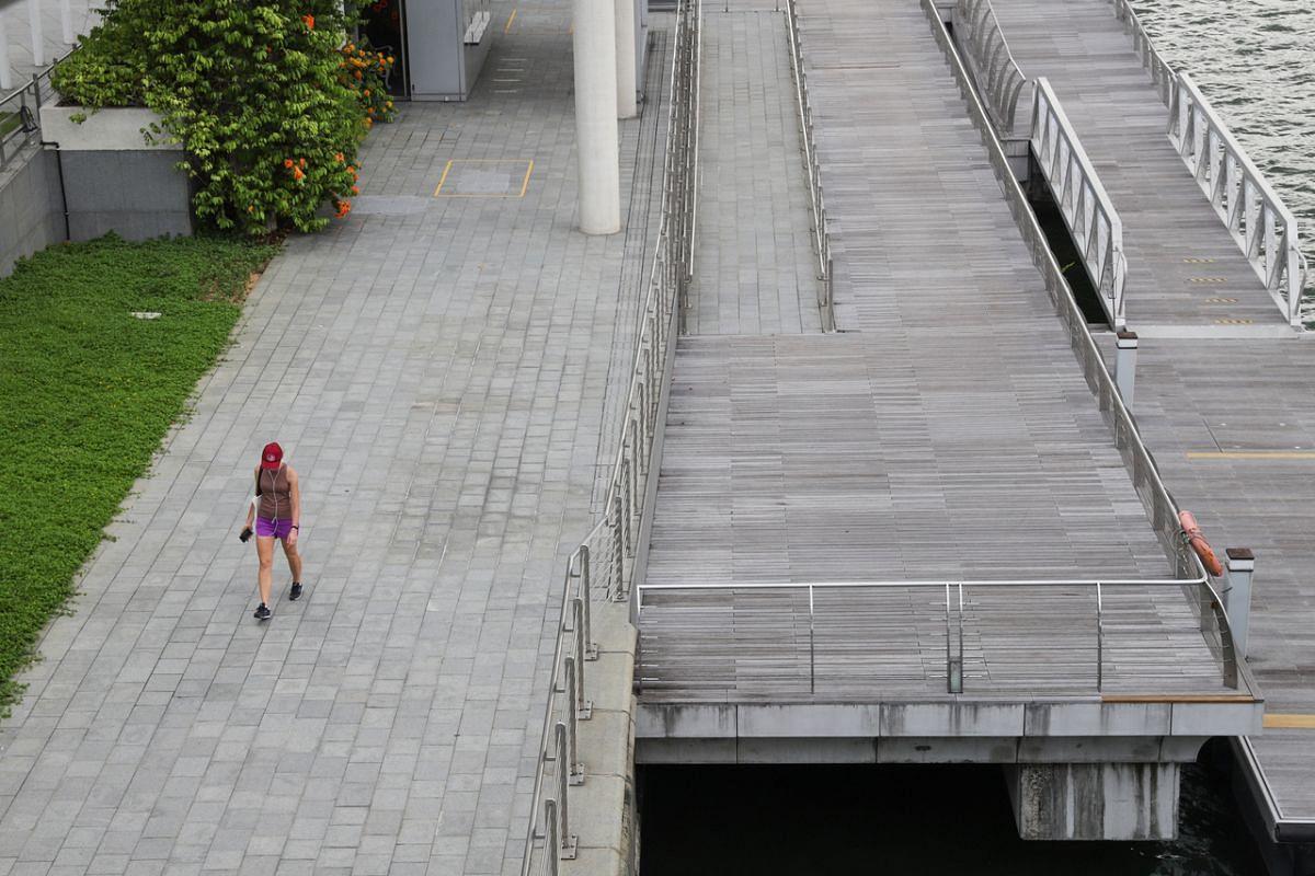 A woman walks along Marina Bay Waterfront Promenade on April 16, 2020.