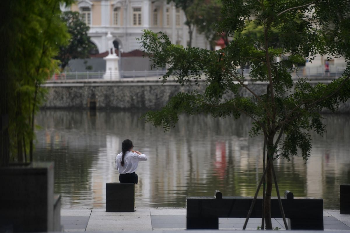 A woman having a meal next to the Singapore River near UOB Tower located in Chulia Street on May 4, 2020.