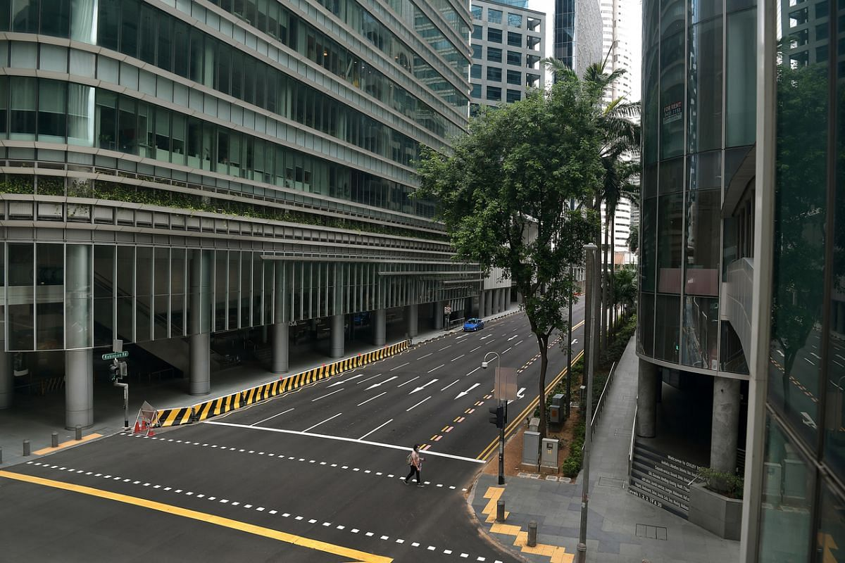 A woman crosses Robinson Road in the empty central business district on April 28, 2020.