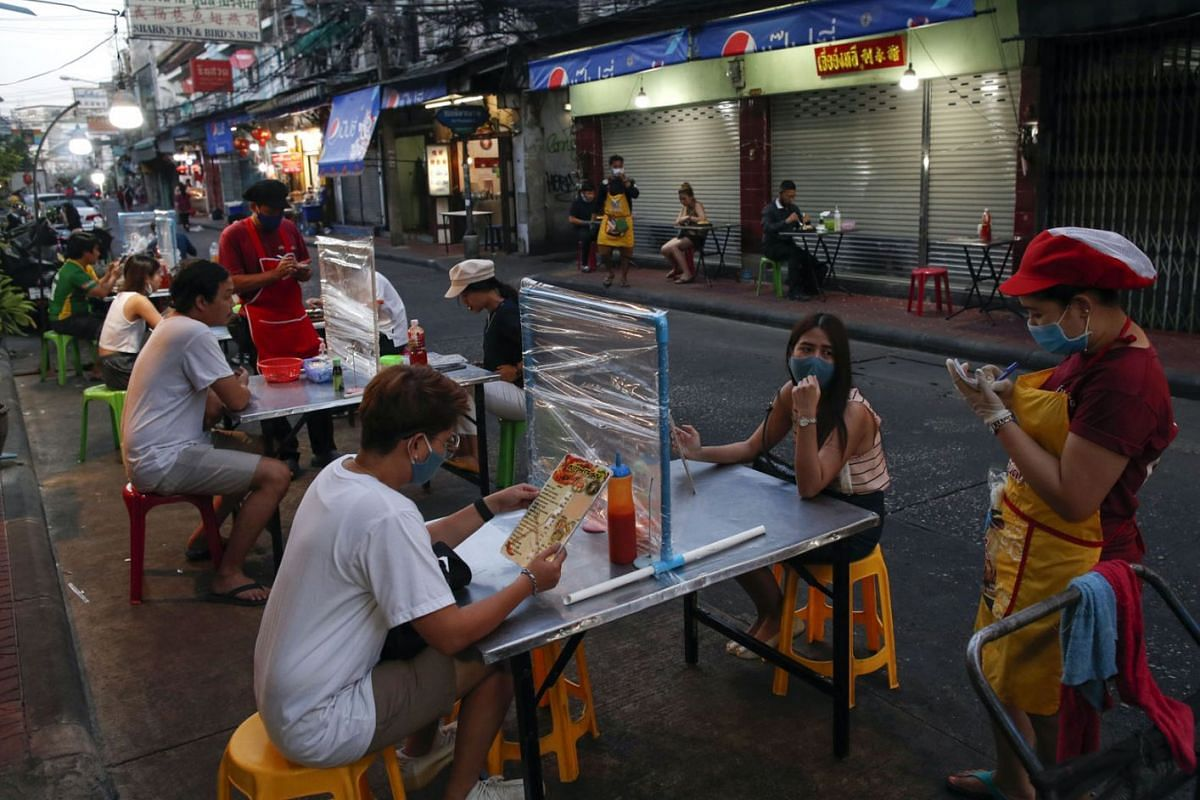 People eat street food at a table dIvided with a plastic shield to prevent the spread of the Covid-19 coronavirus after the government allowed dine-in services as part of the easing of lockdown measures in Bangkok, Thailand, May 12, 2020. PHOTO: EPA-