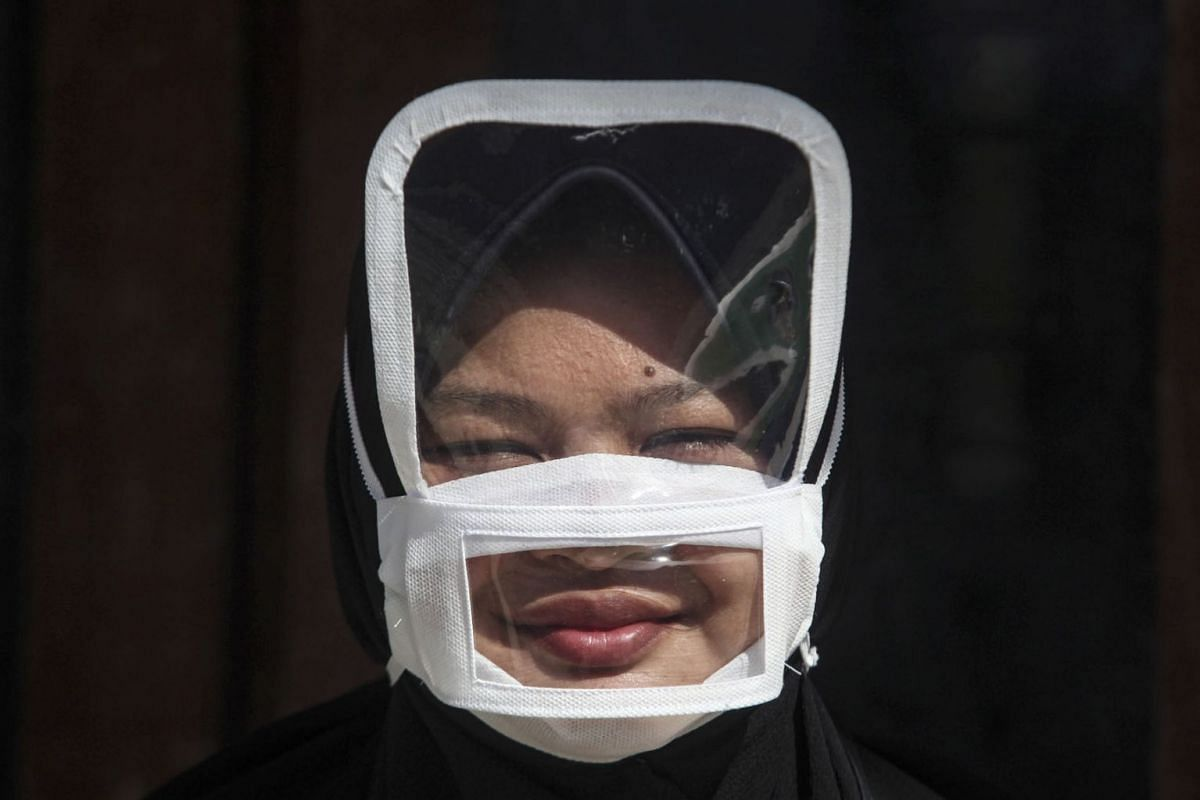 An Indonesian woman Ragil, puts on a transparent cover face mask with additional face shield amid the coronavirus pandemic in Yogyakarta, Indonesia, May 13, 2020. PHOTO: EPA-EFE