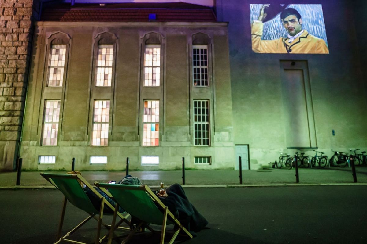 Residents Elias Brandelik (L) and Verena Grass sit in sun chairs and watch the movie 'Loving Vincent' as a projection on a facade in Berlin, Germany, May 14, 2020. PHOTO: EPA-EFE