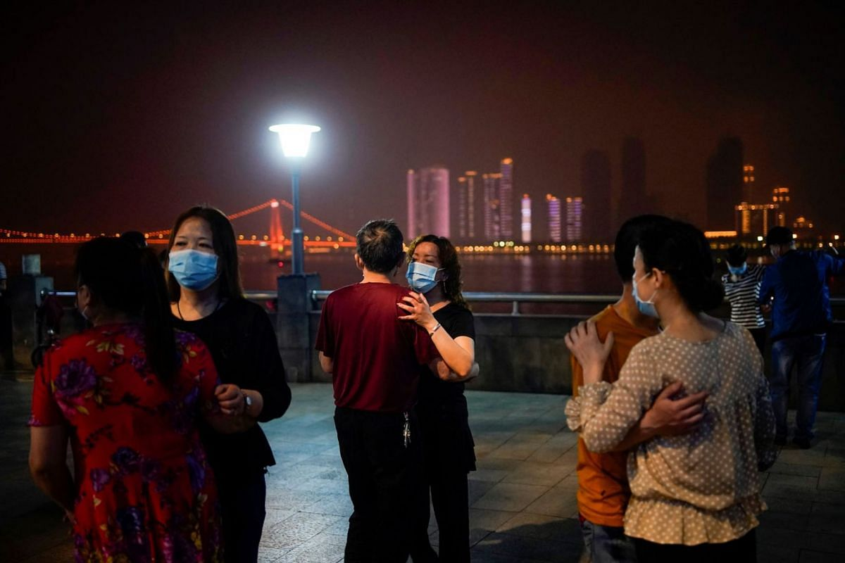 People wearing protective face masks dance under the Yangtze River Bridge in Wuhan, the Chinese city hit the hardest by the coronavirus disease outbreak, in Hubei province, China, May 14, 2020. PHOTO: REUTERS