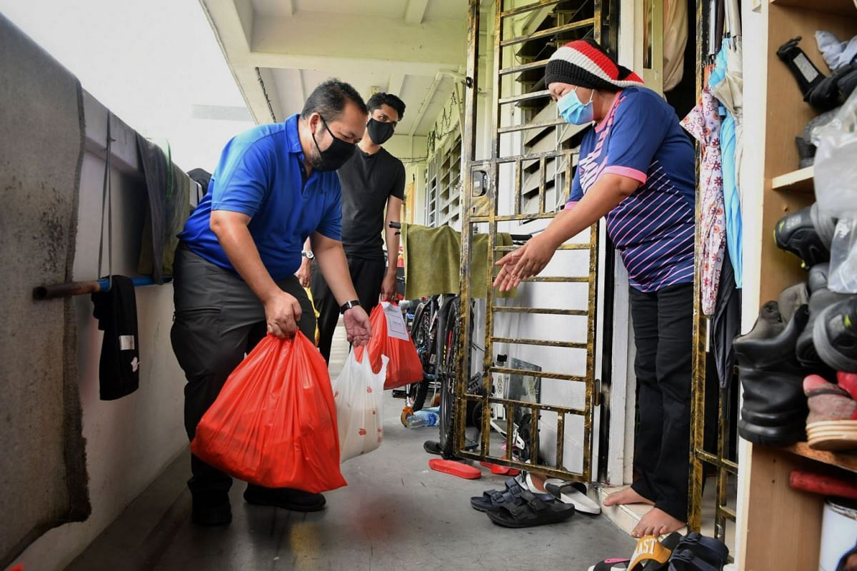 Volunteers from Muhammadiyah Association, Musa Mohamad Sahir, 44, and Hans Ashrie, 26, observe safe distancing as they deliver food items and financial aid to beneficiary Siti Wahidah, 48, a housewife, at her home, in a photo taken on May 15, 2020. P
