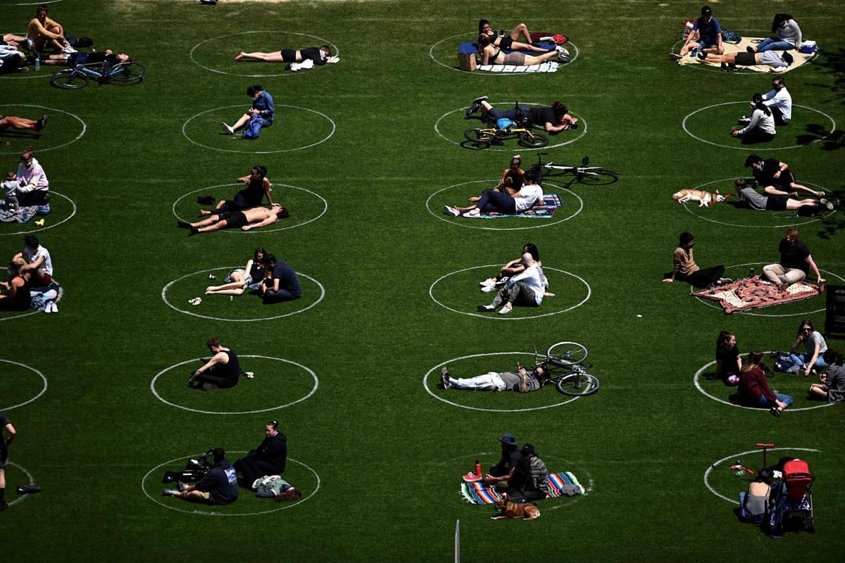 People are seen practicing social distancing in white circles in Domino Park, during the Covid-19 pandemic on May 17, 2020, in the Brooklyn borough of New York City. PHOTO: AFP