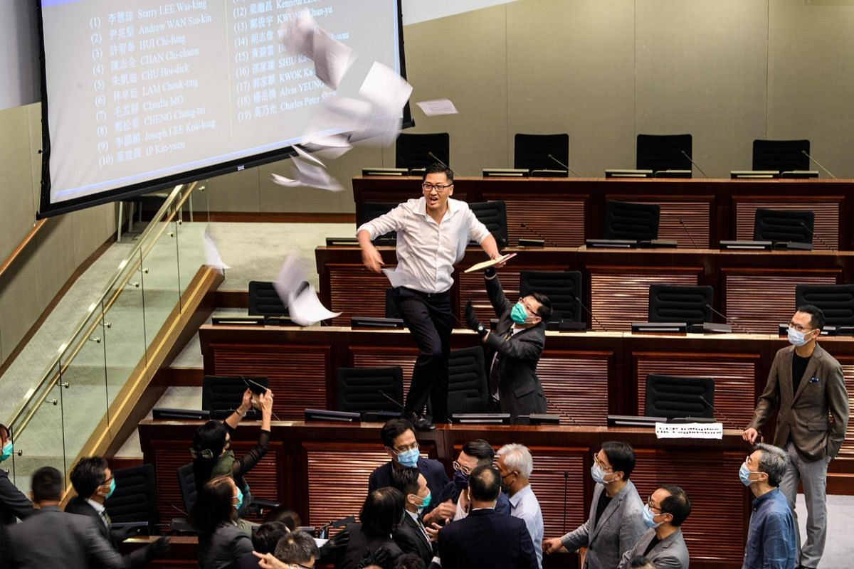 Pan-democratic politician Lam Cheuk-ting (top, centre) throws papers torn from the Legco rulebook during a scuffle between other pro-democracy lawmakers and pro-Beijing lawmakers at the House Committee's election of chairpersons, presided by pro-Beij