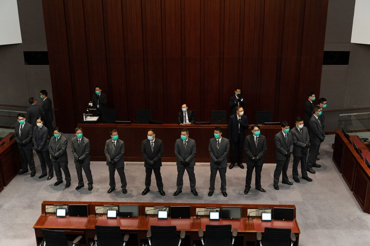 Mr Chan Kin-por, chairman of the Finance Committee at the Legislative Council (centre), is surrounded by security officers as he sits in the chairperson's podium ahead of a meeting to elect a new chairperson for the House Committee at the Legislative