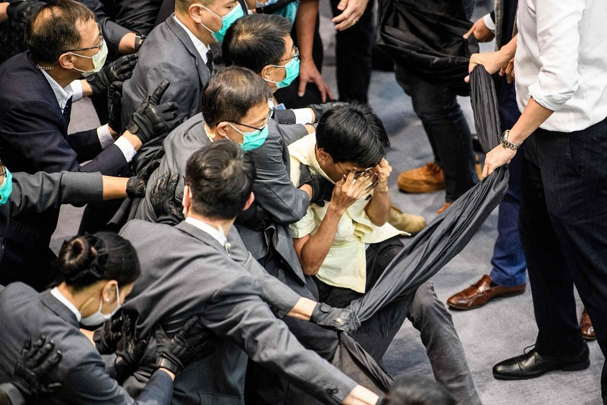 Pro-democracy lawmaker Eddie Chu (centre, right) is surrounded by security during a scuffle with pro-Beijing lawmakers at the House Committee's election of chairpersons, presided by pro-Beijing lawmaker Chan Kin Por (not seen) at the Legislative Coun