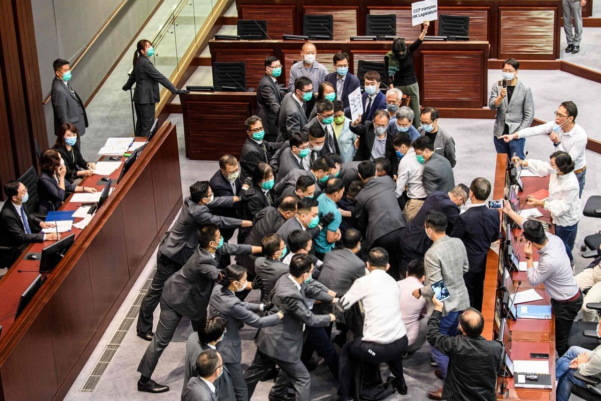 Pro-democracy and pro-Beijing lawmakers scuffle at the House Committee's election of chairpersons, presided by pro-Beijing lawmaker Chan Kin Por (far left) at the Legislative Council, on May 18, 2020.