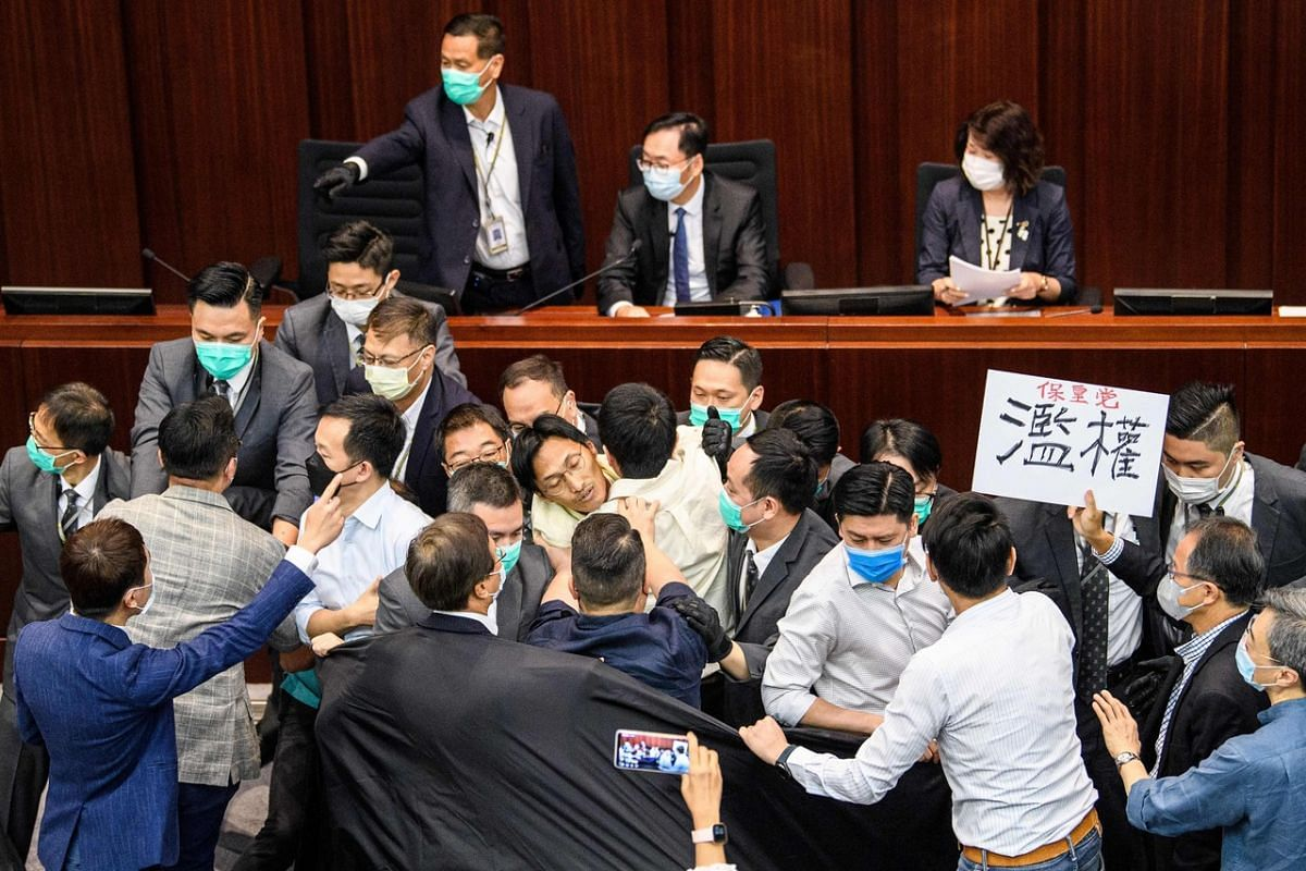 Pro-democracy and pro-Beijing lawmakers scuffle at the House Committee's election of chairpersons, presided by pro-Beijing lawmaker Chan Kin Por (top, centre) at the Legislative Council, on May 18, 2020.