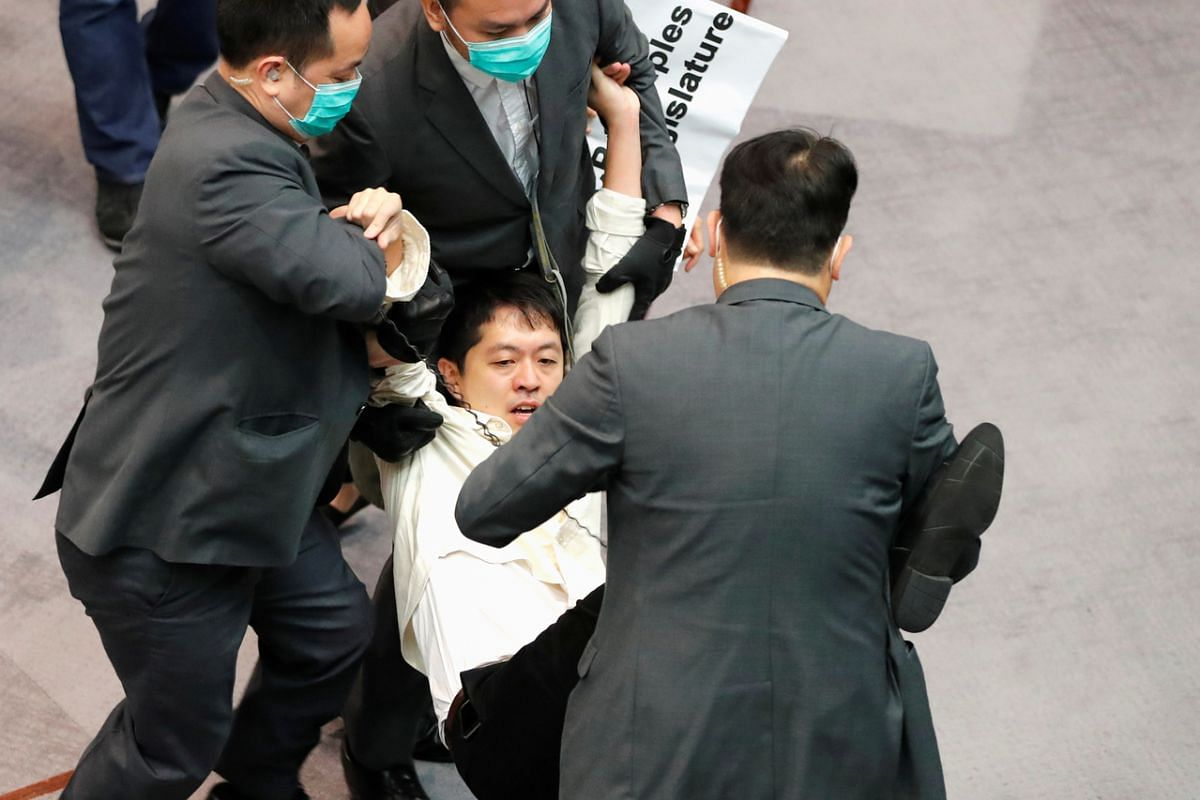 Pan-democratic legislator Hui Chi-fung is being taken away by security during Legislative Council's House Committee meeting, on May 18, 2020.