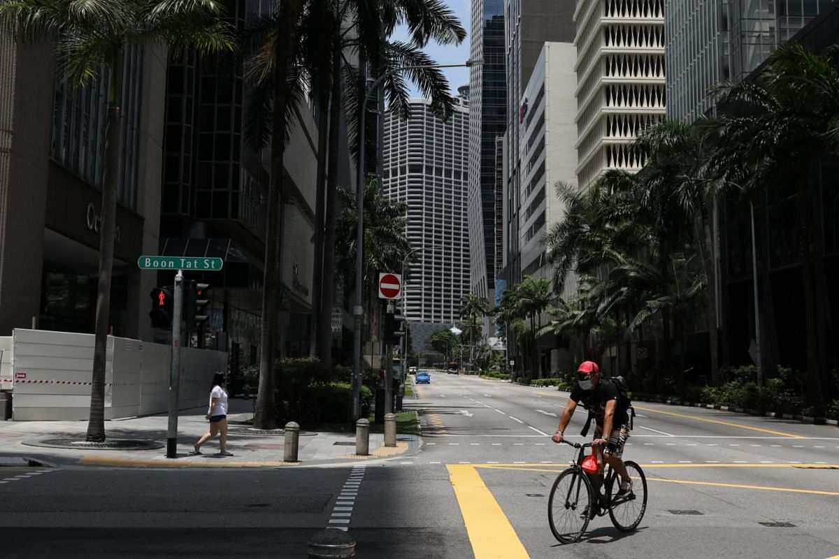 Empty streets in the central business district on April 14 after circuit breaker measures were put in place to pre-empt escalating coronavirus infections. A cyclist with a surgical mask, riding his bicycle at the junction of Boon Tat Street and Cecil