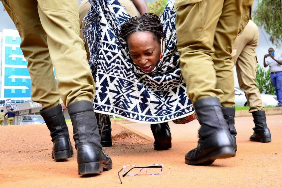 Ugandan academic Stella Nyanzi looks at her glasses as police officers detain her for protesting against the way that government distributes the relief food and the lockdown situation to control the spread of the coronavirus disease outbreak in Kampa