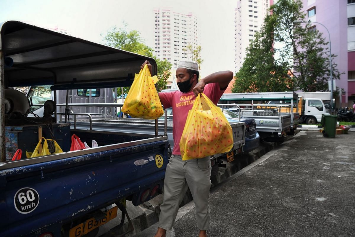 Zahirul Islam, a site supervisor from Bangladesh, loading groceries onto a vehicle in Little India on May 19, 2020. He is buying a week's worth of food for six people. He is among 85,000 foreign workers staying in flats, hotels and condominiums fol