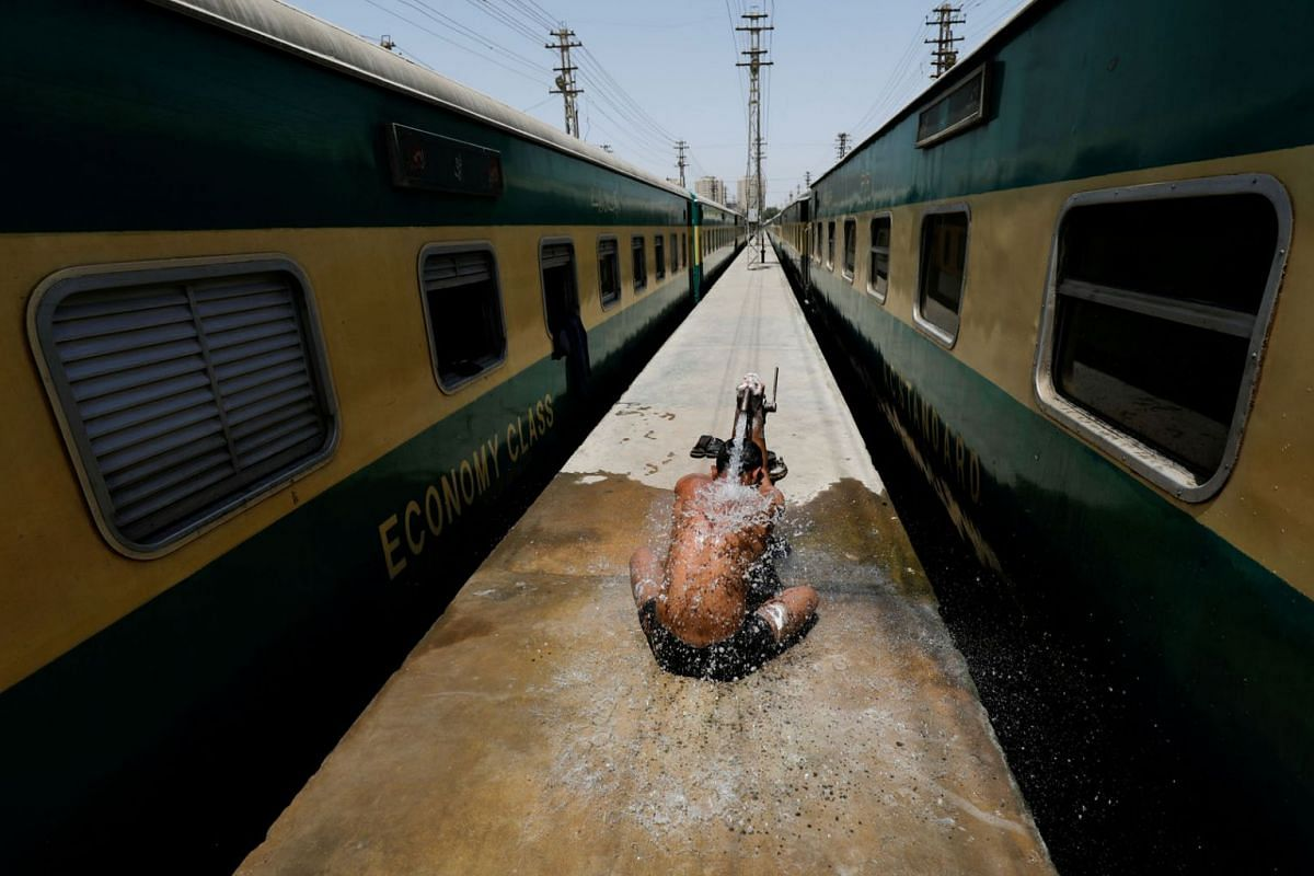 A railway worker takes a bath during hot and humid weather, after Pakistan started easing the lockdown restrictions and allowed to resume passenger trains from tomorrow, as the outbreak of the coronavirus disease continues, in Karachi, Pakistan May 1