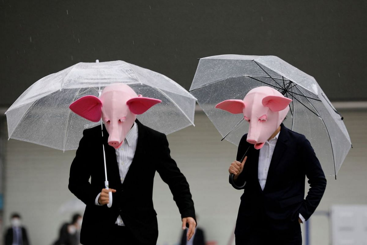 Youtubers wearing masks of pigs film a video at a shopping district amid the coronavirus  outbreak in Tokyo, Japan, May 19, 2020. PHOTO: REUTERS