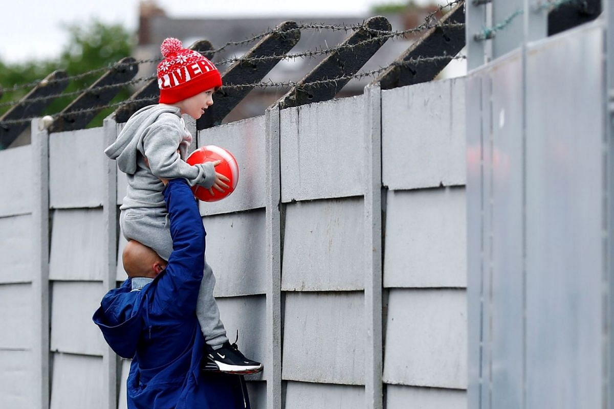 A Liverpool fan is held up as he looks over a fence to watch training at Melwood following the outbreak of the coronavirus disease in Liverpool, Britain on May 19, 2020. PHOTO: REUTERS