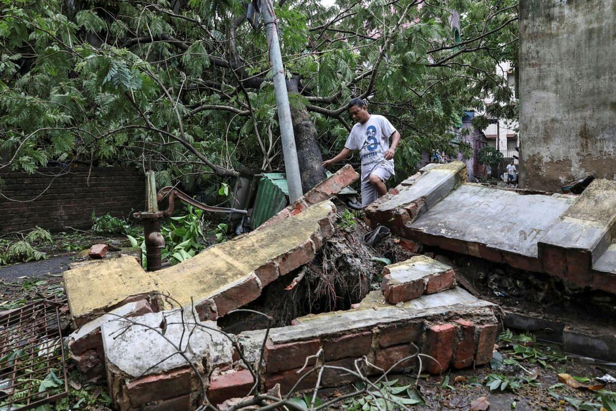 A man walks over a collapsed wall after cyclone Amphan made landfall in Kolkata, India, May 21, 2020. PHOTO: REUTERS