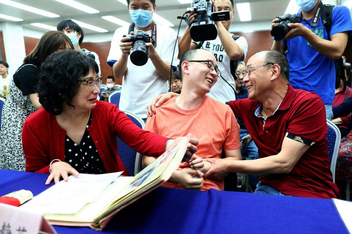 A photo taken on May 18, 2020 shows Mao Yin (C) speaking with his mother Li Jingzhi (L) and father Mao Zhenping (R) in Xian, in China's northern Shaanxi province.  A Chinese man who was kidnapped as a toddler 32 years ago has been reunited with his b
