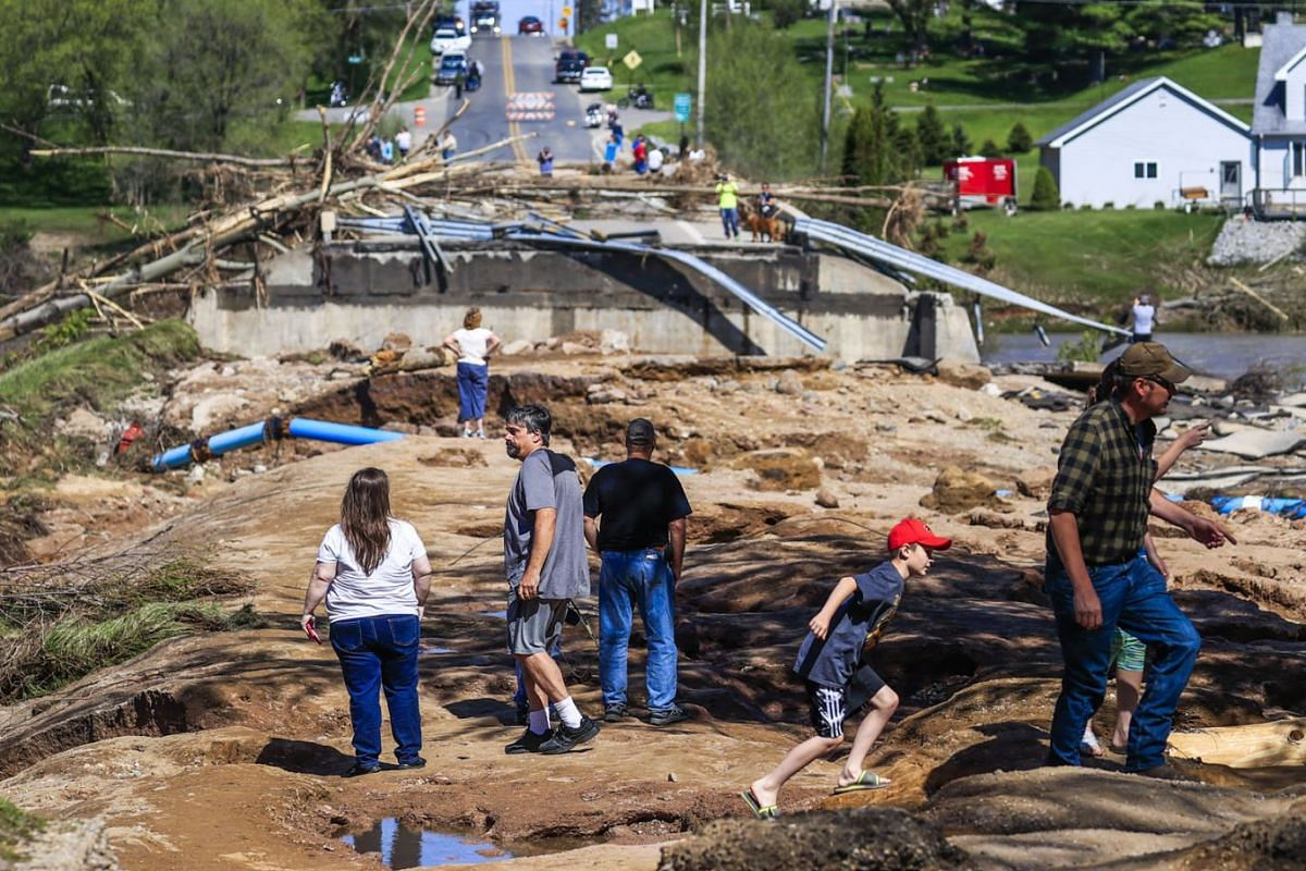People look at damage to a road and bridge after the Edenville dam was breached near Edenville, Michigan, USA, May 20, 2020. The dam at Wixom Lake gave way after heavy rains, sending water downstream and causing the Sanford Dam to give way. Nearly 10