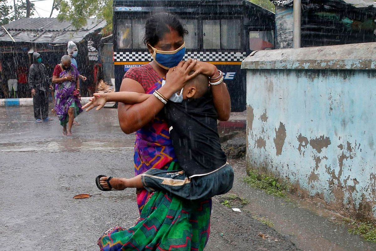 A woman carries her son as she tries to protect him from heavy rain while they rush to a safer place, following their evacuation from a slum area before Cyclone Amphan makes its landfall, in Kolkata, India, May 20, 2020. PHOTO: REUTERS