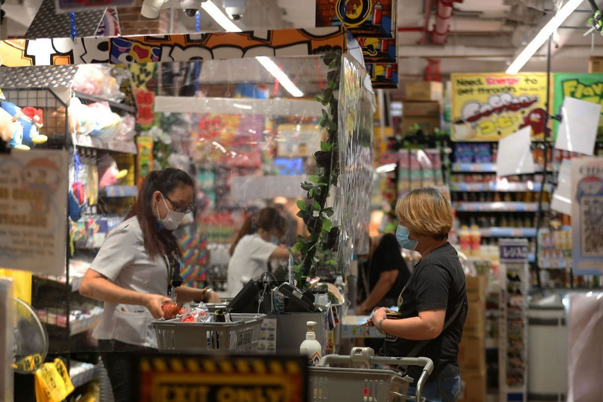 A cashier attends to a customer behind a plastic shield at Don Don Donki in JCube on May 20, 2020. PHOTO: THE STRAITS TIMES/TIMOTHY DAVID
