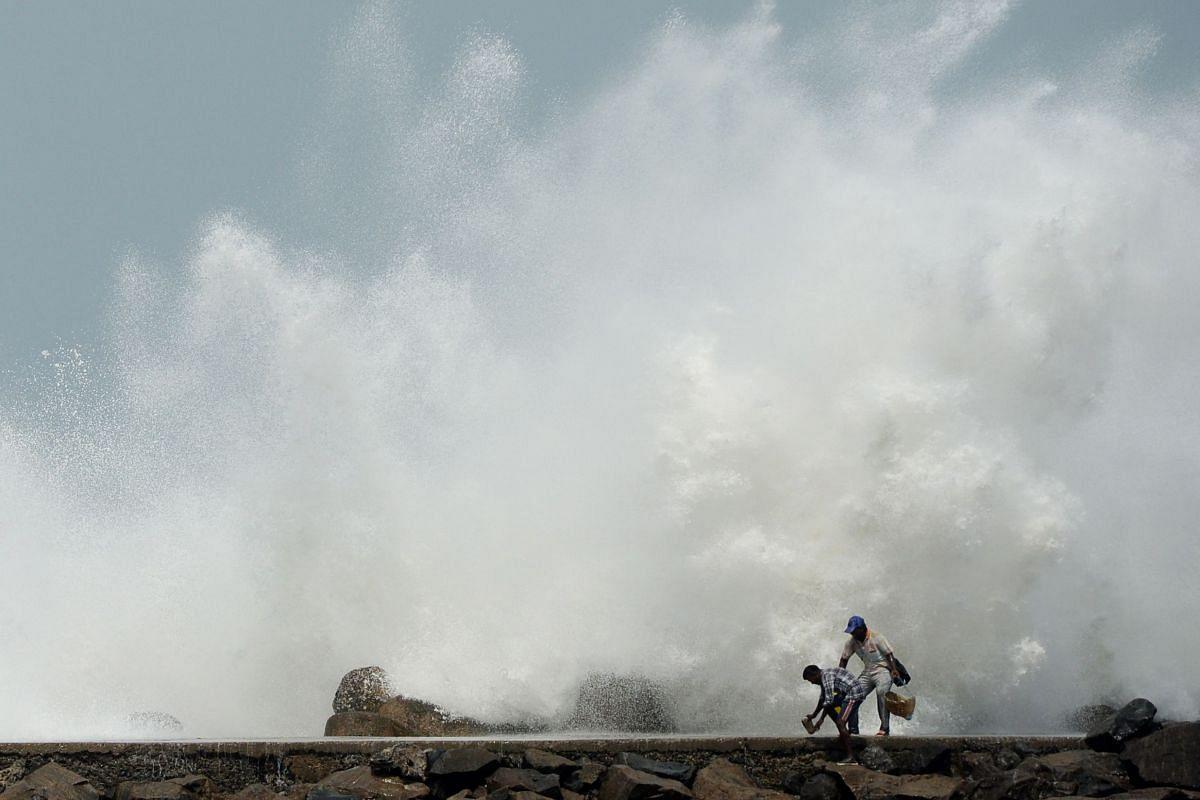 Men walk past as waves hit a breakwater at Kasimedu fishing harbour in Chennai on May 19, 2020.