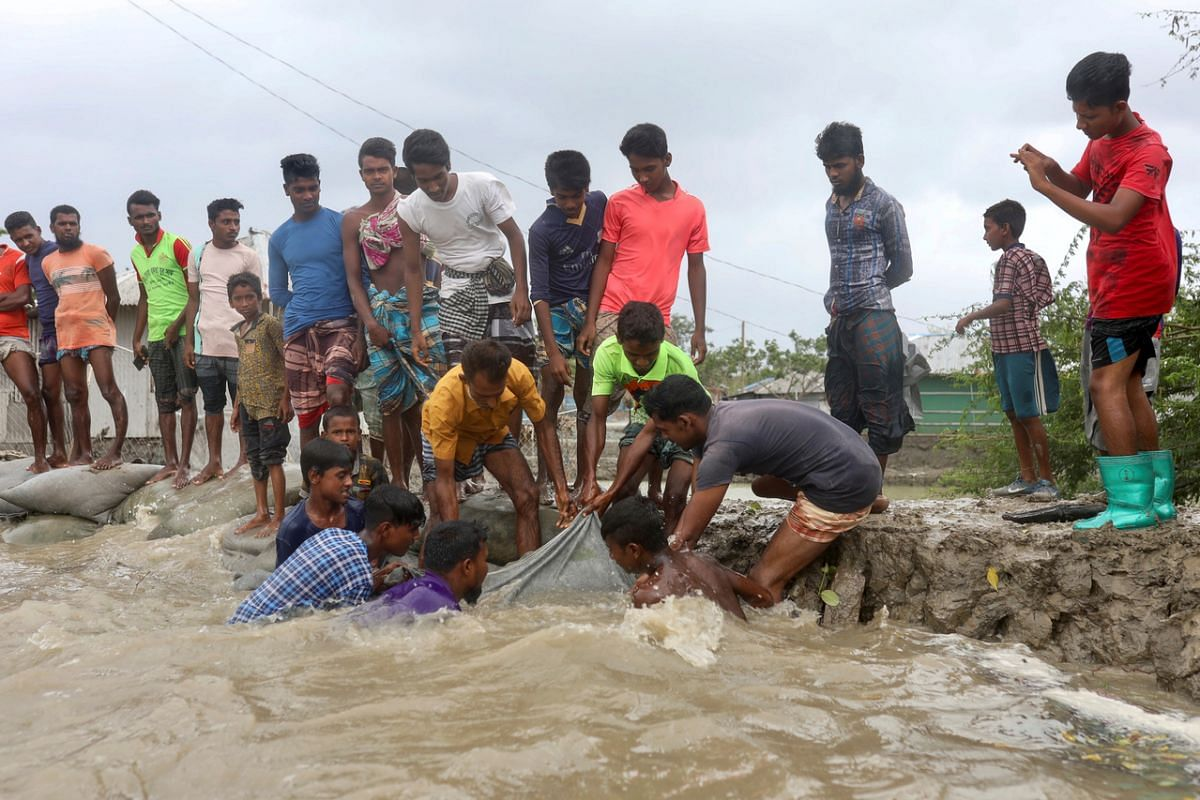 Locals try to reinforce an embankment before cyclone Amphan makes landfall in Gabura, Bangladesh, on May 20, 2020.