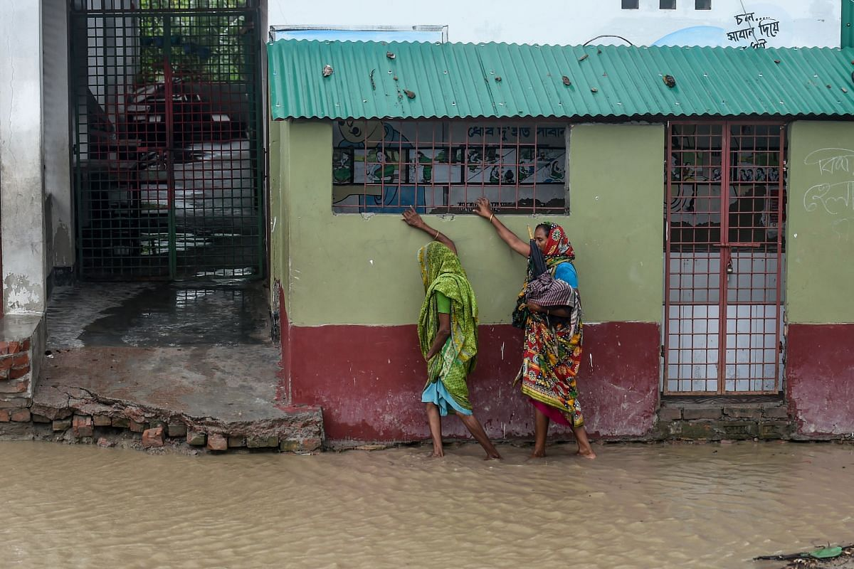 Residents walk along a house on a flooded street heading to a shelter, in Dacope, Khulna, on May 20, 2020.