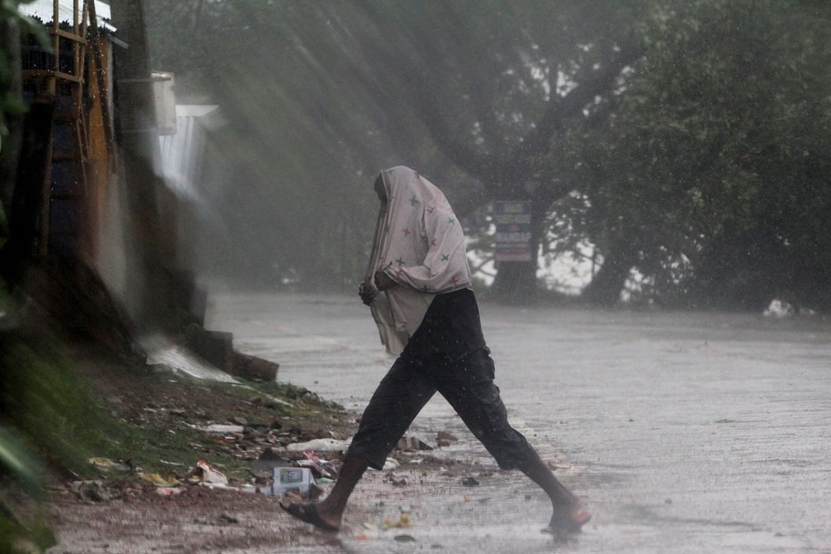 A man walks in heavy rain and wind as cyclone Amphan approaches Odisha, India, on May 20, 2020.