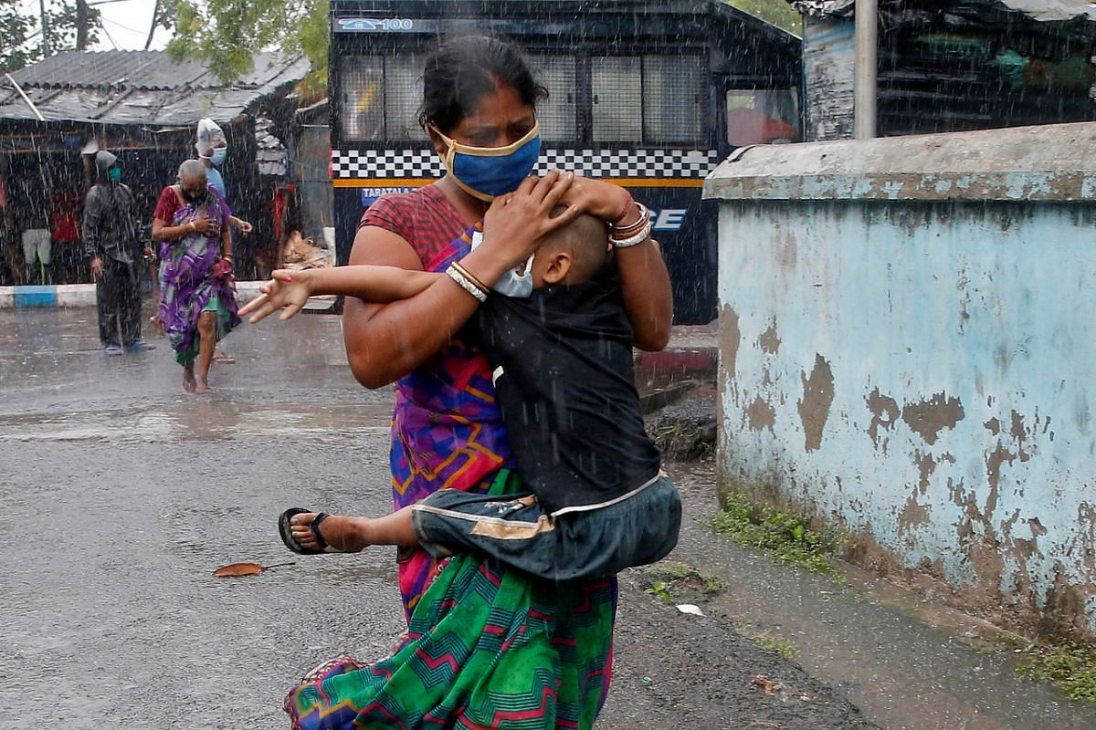 A woman shields her son from heavy rain as they rush to safety and shelter in Kolkata, India, on May 20, 2020.