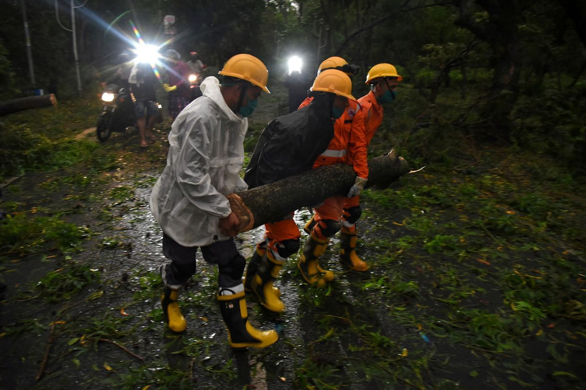 Members of National Disaster Rescue Force remove a branch of an uprooted tree after cyclone Amphan made landfall near the border between the eastern states of West Bengal and Odisha, India, on May 20, 2020.