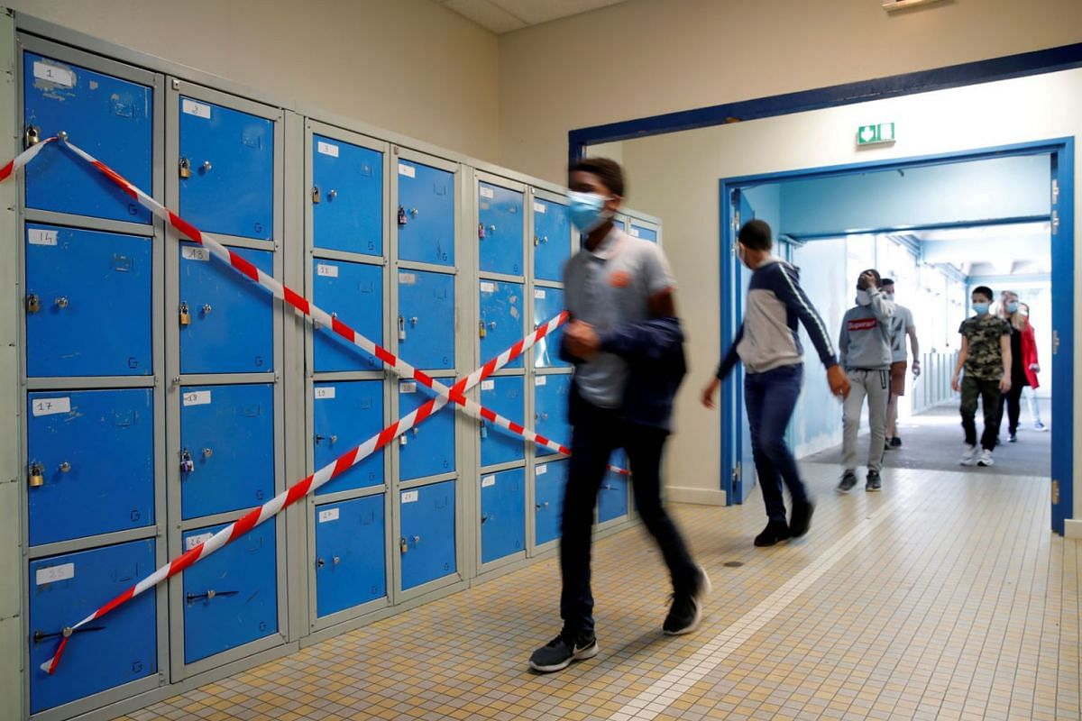 Students maintain social distancing as they walk past taped up lockers at the College Rosa Parks school during its reopening in Nantes, France, on May 20, 2020. PHOTO: REUTERS