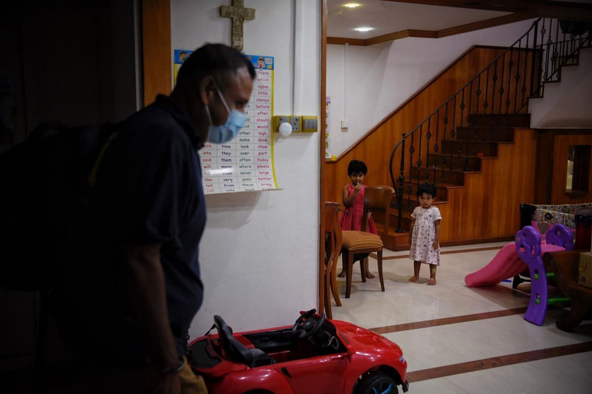 The pastor arrives home at around 10pm. His daughters Emmanuella (centre), four, and Daniella, two, wait for him to shower so that they can hug him.