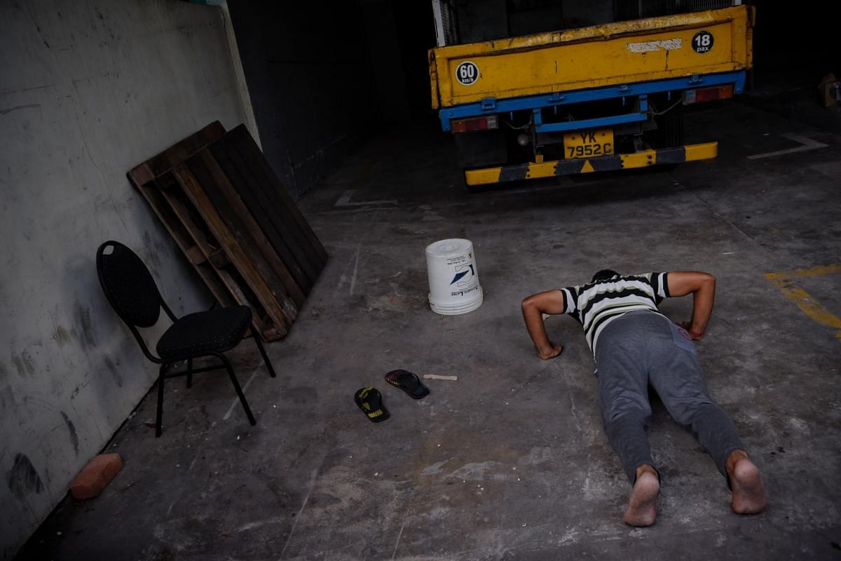 A migrant worker does push-ups during a challenge organised by a 31-year-old AGWO to motivate FCD residents during the circuit breaker. The top winner won a refurbished Iphone.